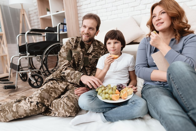 A disabled father in military uniform is eating fruits. Premium Photo