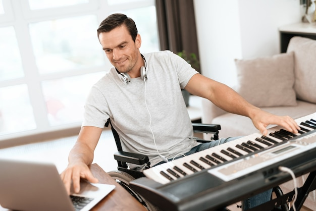 Disabled man composing song with electric piano. Premium Photo