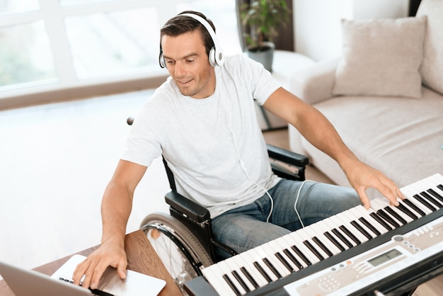 Disabled man composing song with synthesizer Premium Photo