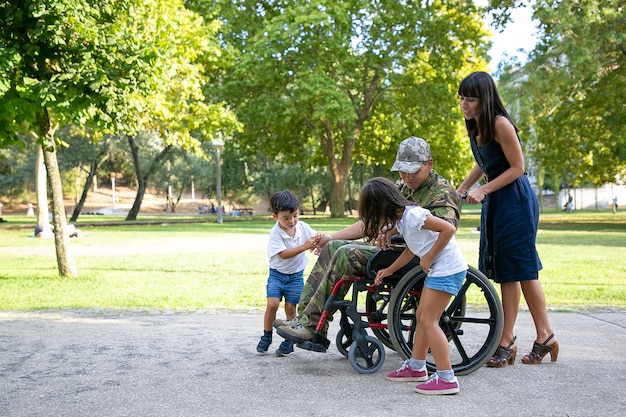 かわいい子供たちと話している障害のある軍の父。家族と一緒に屋外でカモフラージュの制服を着た白人の中年のお父さん。車椅子を押すかわいいお母さん。家族の再会と戦争の概念のベテラン 無料写真