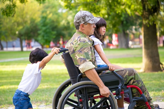 公園で2人の子供と一緒に歩いている障害のある軍のベテラン。お父さんの膝の上に座っている女の子、車椅子を押す男の子。戦争または障害の概念のベテラン 無料写真