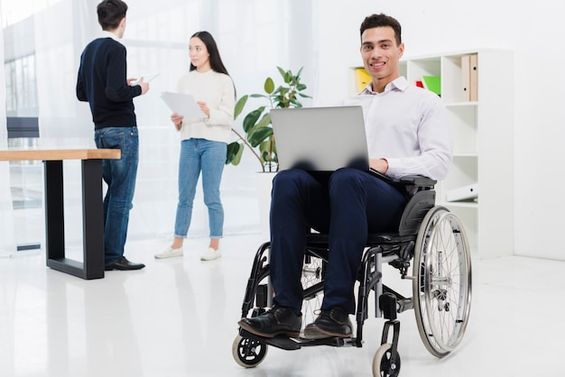 A disabled smiling young businessman sitting on wheelchair with laptop in front of business colleague Free Photo