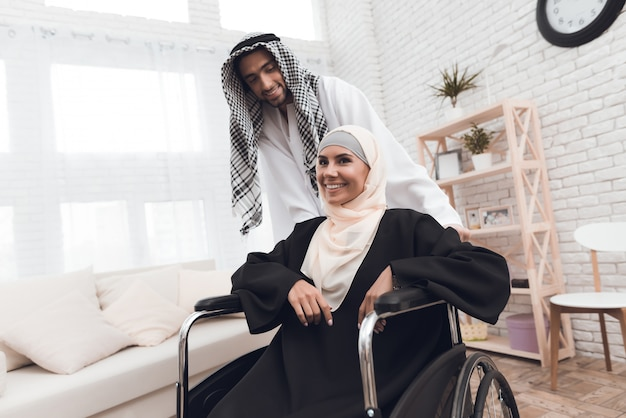 A disabled woman in a hijab is sitting in a wheelchair. Premium Photo