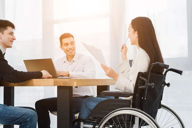 Disabled young businesswoman sitting on wheelchair discussing with his male colleague in office Free Photo
