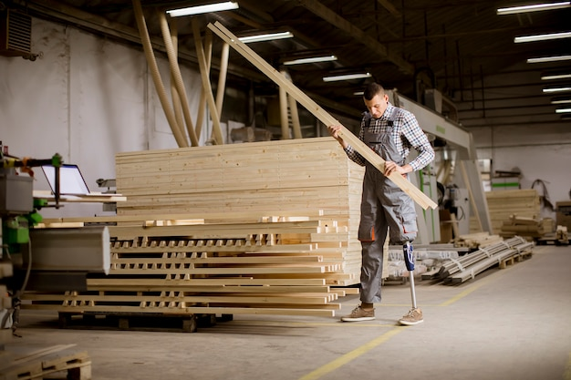 Disabled young man with an artificial leg is working at furniture factory Premium Photo