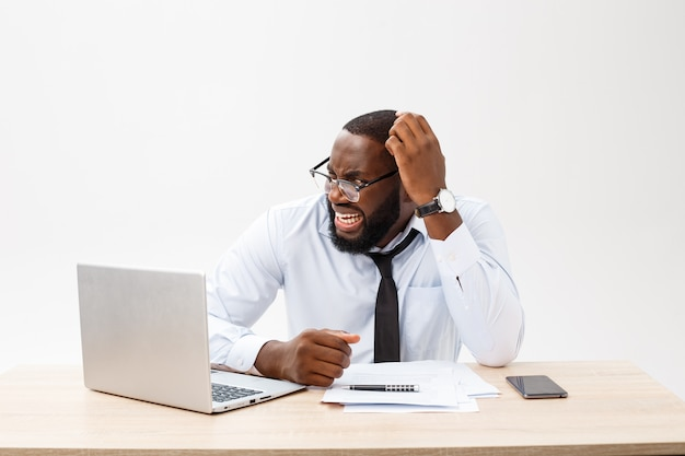 Disappointed african businessman is dazed and confused by a mistake in official documents Premium Photo