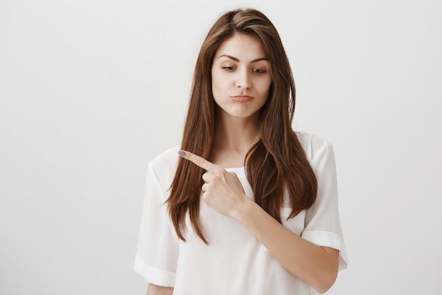 Разочарованная милая девушка смотрит вниз с сожалением, указывая пальцем влево Бесплатные Фотографии