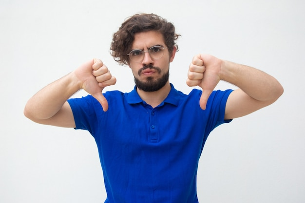 Disappointed dissatisfied customer making dislike gesture Free Photo
