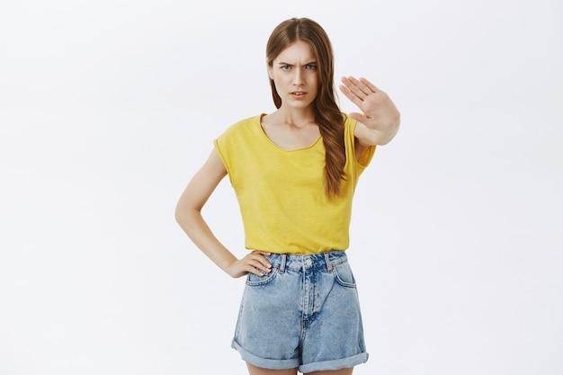 Разочарованная хмурящаяся девушка показывает жест стоп, запрещает или отказывается что-то всепоглощающее Бесплатные Фотографии