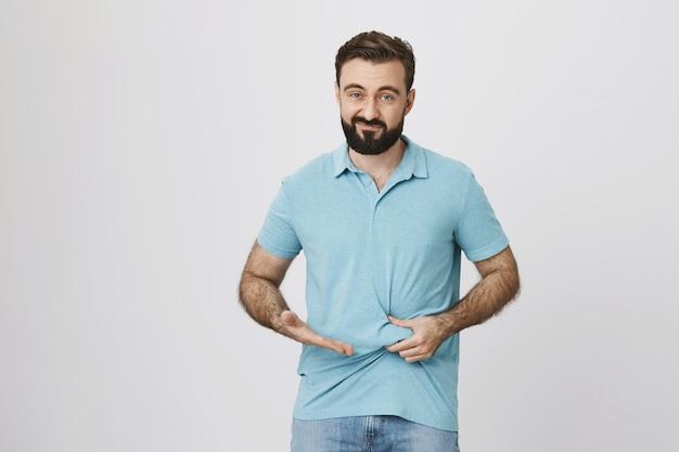Разочарованному парню нужно похудеть, показывая толстый живот Бесплатные Фотографии