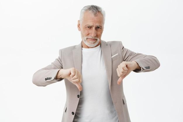 Разочарованный старший бизнесмен показывает палец вниз и недовольно хмурится Бесплатные Фотографии