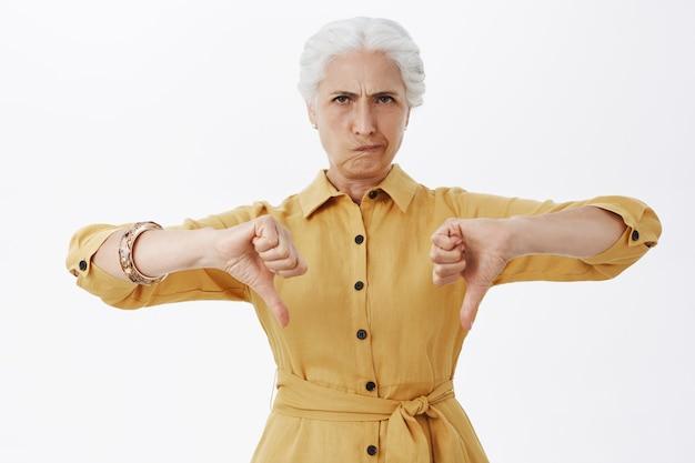 Разочарованная старшая дама хмурится и показывает палец вниз Бесплатные Фотографии