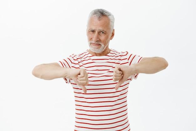 L'uomo anziano deluso in maglietta che mostra il pollice verso il basso, mostra il gesto di avversione Foto Gratuite