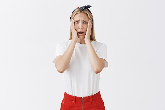 Разочарованная шокированная молодая девушка выглядит расстроенной и обеспокоенной Бесплатные Фотографии