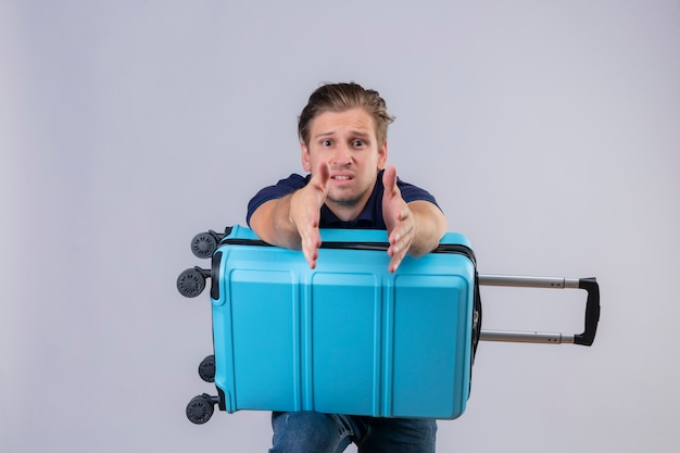Disappointed young handsome traveler guy standing with suitcase stretching hands out  asking for help Free Photo