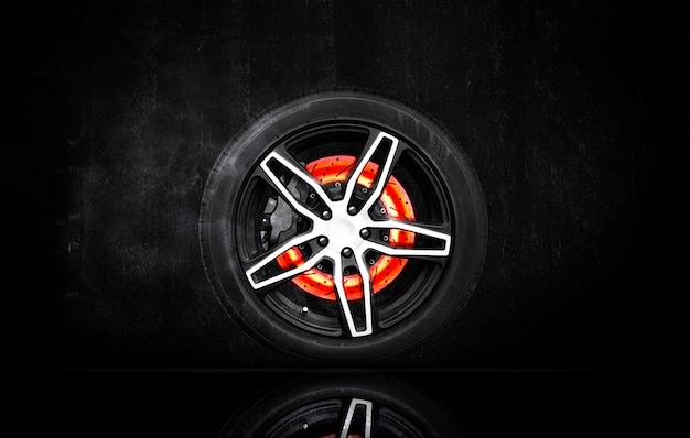 Disc brake scratch burning in a racing wheel on black cement wall background. Premium Photo