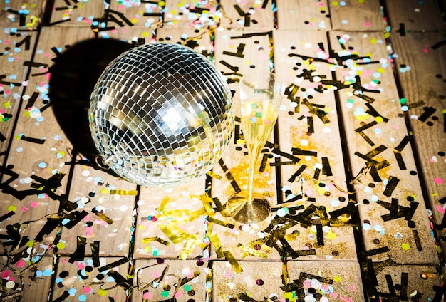 Disco ball and glass of drink between confetti Free Photo