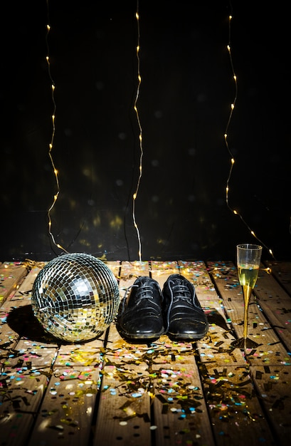 Disco ball, man's boots and glass of drink between confetti Free Photo