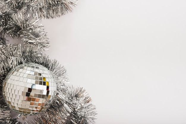 Disco ball with tinsel on white table Free Photo