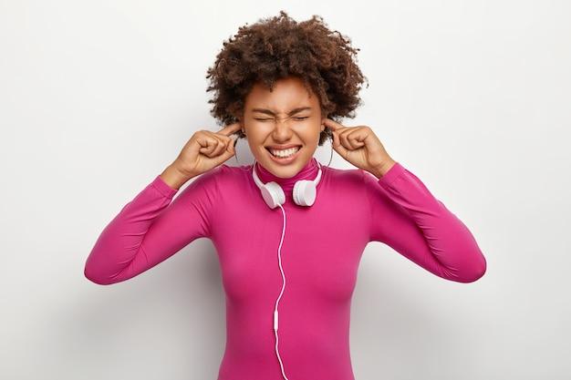 Donna afro scontenta con i capelli ricci, inserisce le dita nei fori delle orecchie, ignora il rumore sgradevole Foto Gratuite