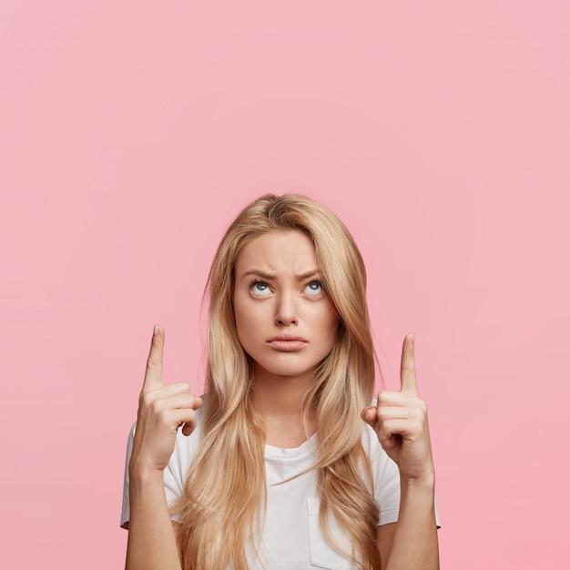Недовольная симпатичная блондинка указывает указательными пальцами над головой на пустое место для копирования, недоуменно смотрит вверх, демонстрируя что-то странное, изолированное над розовой стеной Бесплатные Фотографии