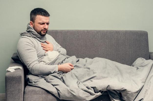 Болезнь. болеем дома. молодой человек болен, лечится дома. боль в груди, затрудненное дыхание. дует нос в салфетку, насморк. инфекция, эпидемия, бактерионоситель. Premium Фотографии