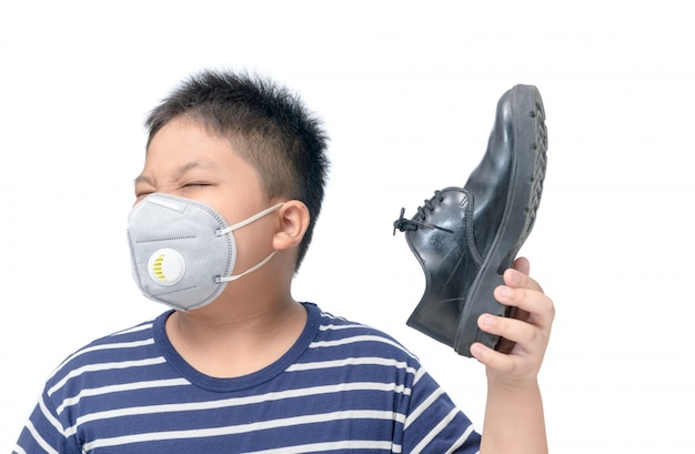 Disgusted boy holding a pair of smelly leather shoes Premium Photo