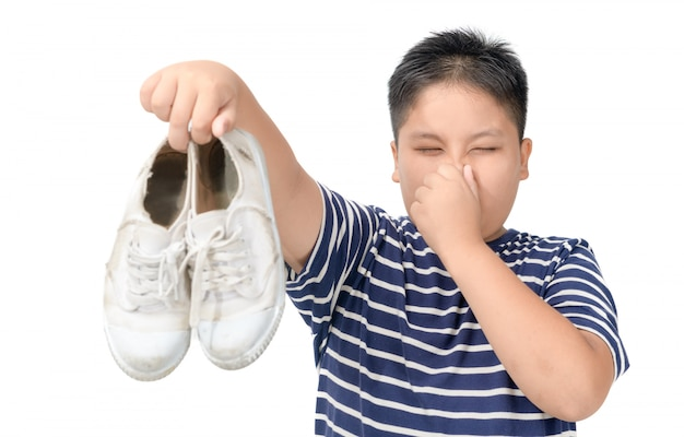 Disgusted fat boy holding a pair of smelly shoes | Premium Photo