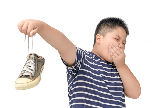 Disgusted fat boy holding a pair of smelly shoes Premium Photo