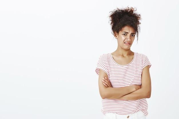 Отвращение невпечатленная женщина с афро-прической позирует в студии Бесплатные Фотографии