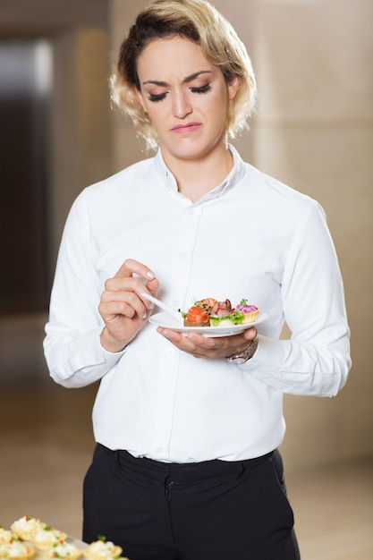 Disgusted woman with exotic snacks at buffet table Free Photo