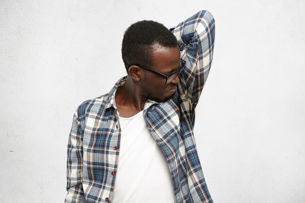 Disgusted young male wearing checkered shirt and glasses smelling wet sweaty armpit after stressful meeting, feeling nauseous, screwing lips. black man can't stand bad smell. hyperhidrosis and hygie Free Photo