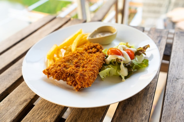 Блюдо рыба в кляре с картофелем фри. рыба на тарелку с картофелем и салатом в летнем кафе. Premium Фотографии