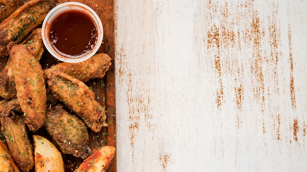 Dish of roasted wings with potato and sauce Free Photo