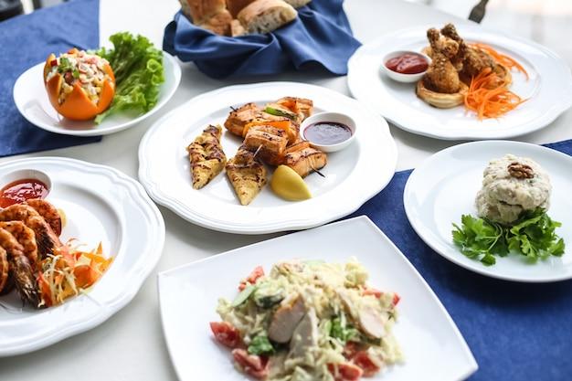 Наборы блюд из цезаря с тунцом, креветки, куриные ножки, вид сбоку Бесплатные Фотографии