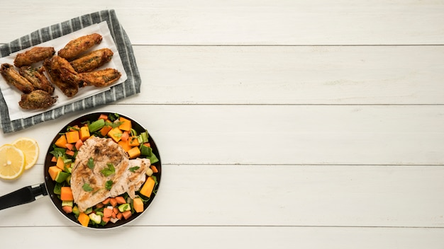 Dish with chicken wings and frying pan of vegetables on wooden desk Free Photo