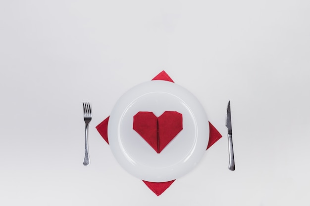 Dish with cutlery and a heart-shaped napkin Free Photo