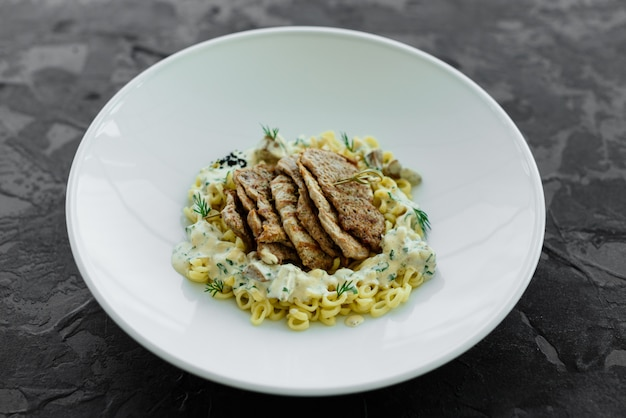 Dish with meat pieces, pasta, greens, sauce from a foie gras and the olive earth Premium Photo