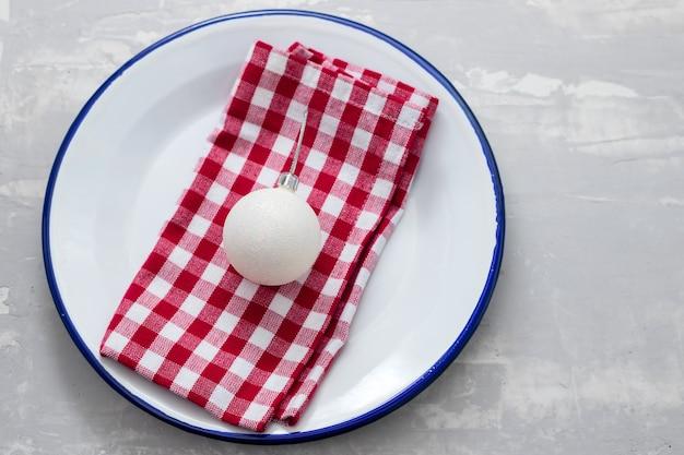 Блюдо с салфеткой и елочной игрушкой на керамическом фоне Premium Фотографии