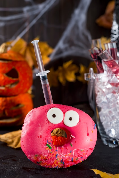 Dishes with glazed donuts, with a red cocktail in a glass tube in a bucket of ice Premium Photo