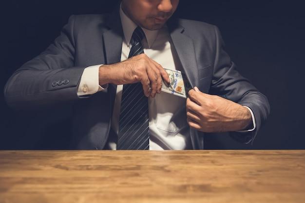 Dishonest businessman putting money, us dollars, into his suit pocket in the dark Premium Photo