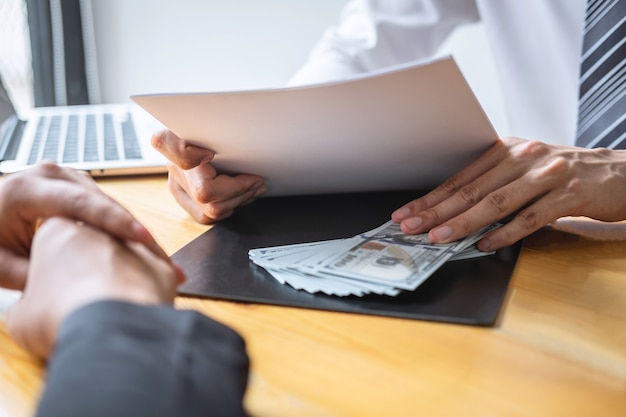 Dishonest cheating in business illegal money, businessman giving bribe money in business people to give success the deal contract of investment, bribery and corruption concept Premium Photo
