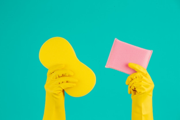 Dishwasher wearing yellow gloves on a blue . Free Photo