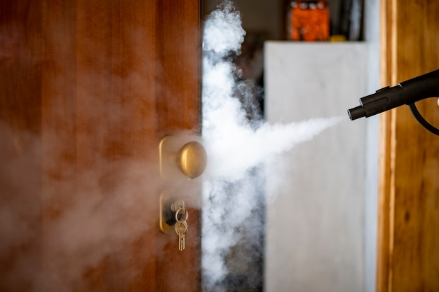 집에서 스팀으로 소독 및 살균, 스팀 흐름은 도어 핸들과 잠금 장치의 키로 전달됩니다. 프리미엄 사진