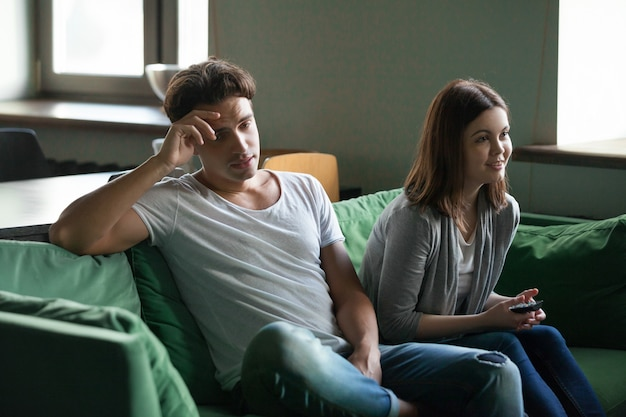 Disinterested boyfriend getting bored while excited girlfriend watching tv series Free Photo