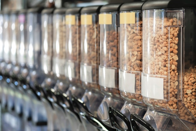 Dispensers with nuts in zero waste shop. new trend alternative buying. zero waste, eco-friendly concept. sustainable lifestyle concept. Premium Photo