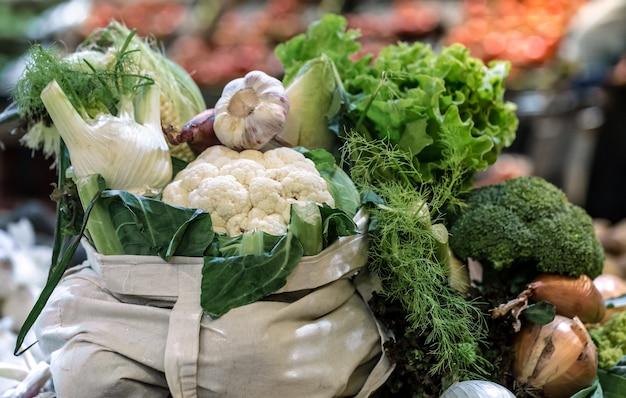 Выставка свежей спелой органической брокколи, салата с зеленью и овощами в хлопковом пакете на фермерском рынке выходного дня Бесплатные Фотографии