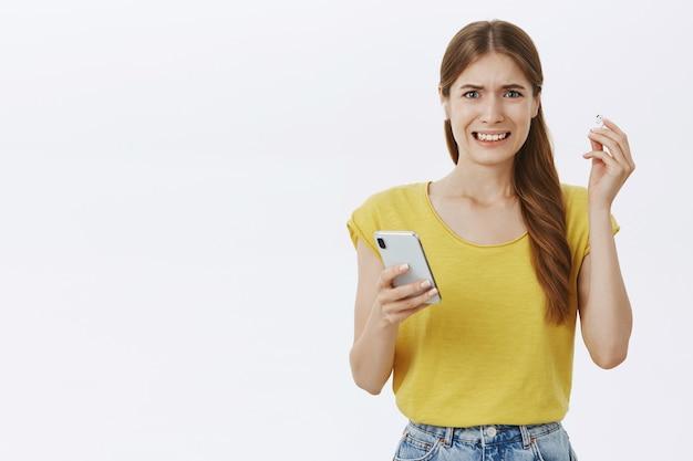 Недовольная и недовольная девочка-джин снимает наушники и морщится от ужасной музыки, держа в руках смартфон Бесплатные Фотографии
