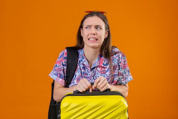 オレンジ色の壁にスーツケースを持ってバックパックで頭に赤いサングラスをかけている不機嫌で恐ろしい若い旅行者女性 無料写真