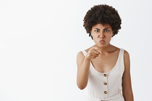Displeased angry and disappointed dark-skinned wife with afro hairstyle, pointing with index finger, frowning, pulling face from anger, being outraged on someone Free Photo
